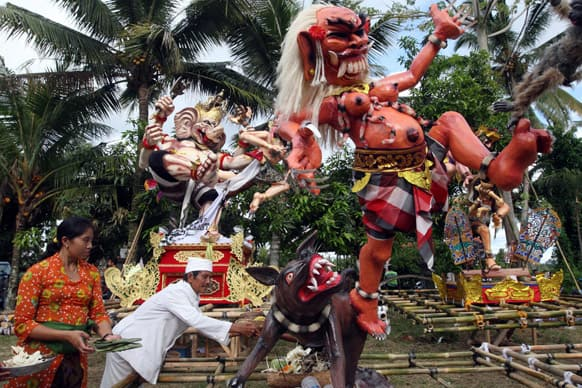 A Balinese priest puts an offering at
