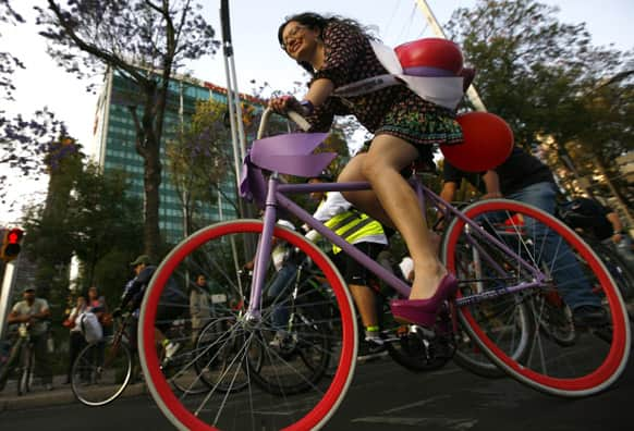 Women ride bikes wearing dresses and high heels along Reforma Avenue in Mexico City.