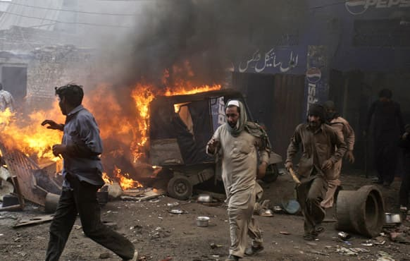 Pakistani men, part of an angry mob, run after burning belongings of Christian families, in Lahore.