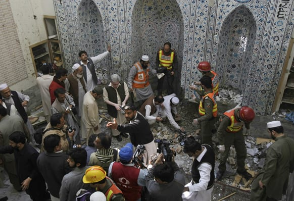 Pakistani security officials and rescue workers examine the site of bomb blast inside a mosque in Peshawar.