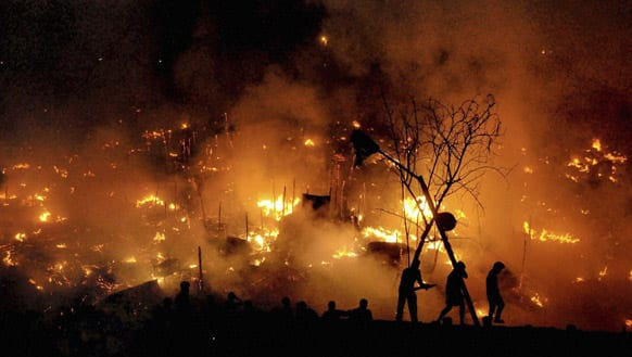 People are silhouetted as a fire engulfs a shanty town in the eastern Indian city of Bhubaneswar. About 300 homes were gutted in the fire, according to reports.
