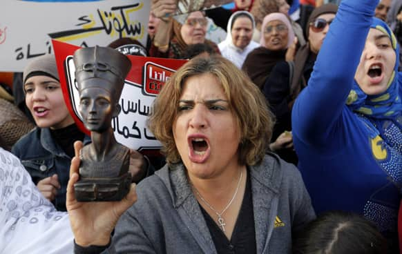 An Egyptian woman raises a statue of pharaonic Queen Hatshepsut, the only woman that ruled Egypt, as she shouts slogans during a demonstration in Cairo.