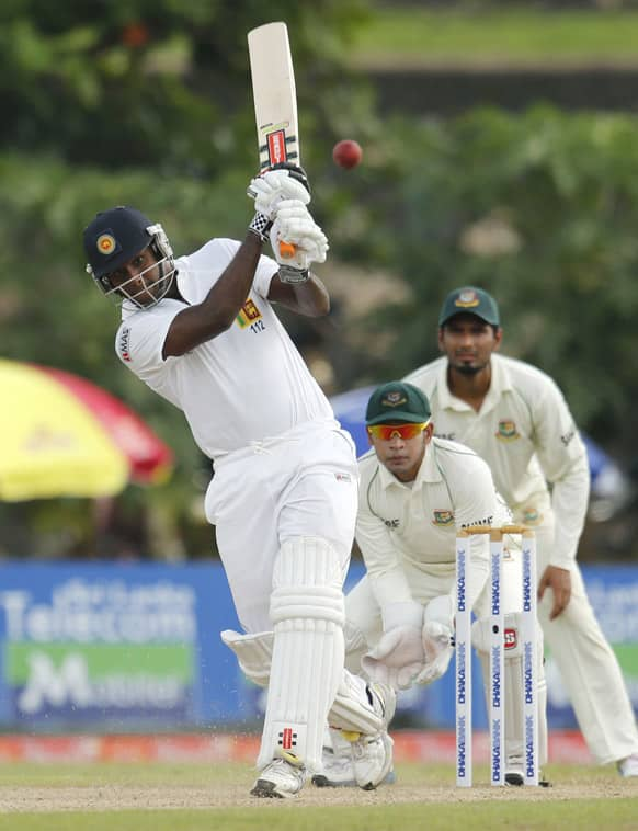Sri Lanka`s captain Angelo Mathews bats in front of Bangladesh`s Mushfiqur Rahim during the first day of their first cricket test match in Galle, Sri Lanka.