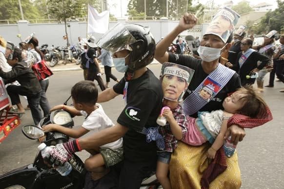 A Cambodian family, wearing a portrait of detained Yoam Bopha, a Boeung Kak lake villager, takes part in a rally to mark the World Women`s Day, in Phnom Penh, Cambodia.