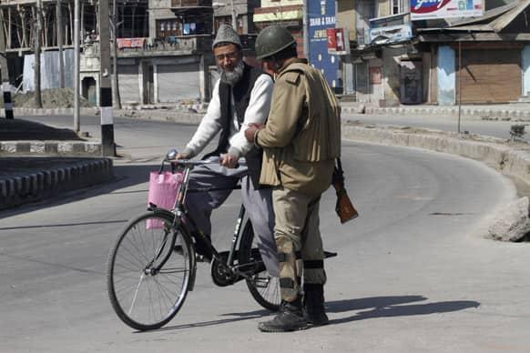 A paramilitary soldier checks the identity card of a civilian during a curfew in Srinagar.