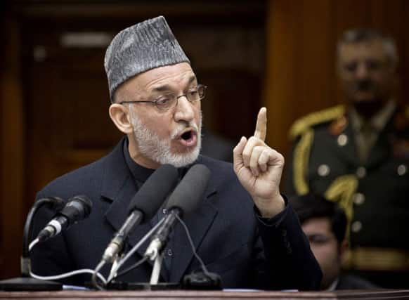 Afghan President Hamid Karzai gestures as he addresses the Afghan Parliament in Kabul.