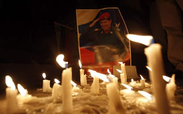 Candles, placed by mourner demonstrators, burn in front of an image of Venezuela`s President Hugo Chavez outside Venezuela`s embassy in Quito, Ecuador. Venezuela`s Vice President Nicolas Maduro announced that Chavez died on Tuesday at age 58 after a nearly two-year bout with cancer.