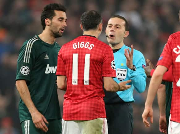 Manchester United`s Ryan Giggs argues with referee Cuneyt Cakir after he gave a yellow card to teammate Nani during their Champions League round of 16 soccer match at Old Trafford Stadium, Manchester, England.