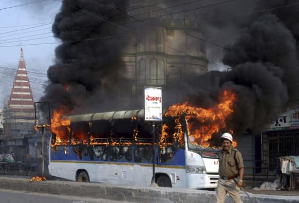 A police man walks past a bus set on fire by protesting teachers in Patna.