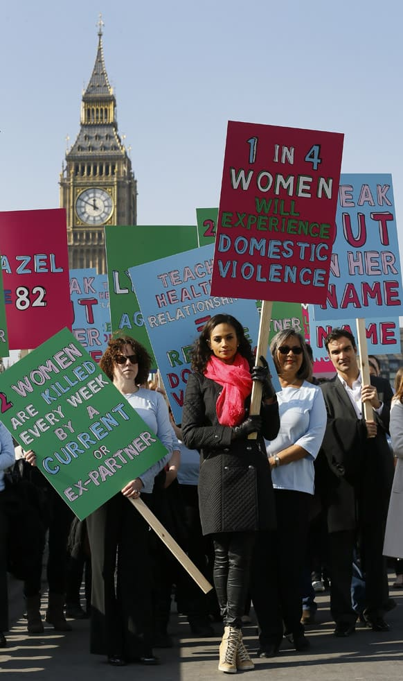 British television presenter Alesha Dixon leads people holding banners during a demonstration against domestic violence near Big Ben in the lead up to Friday`s International Women`s Day, London.