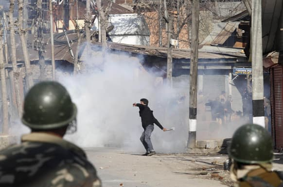 A Kashmiri protester throws a teargas shell back to Indian paramilitary soldiers during a protest in Srinagar.