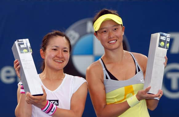 Chang Kai-chen, right, of Taiwan, and Shuko Aoyama of Japan pose with their trophies after defeating Janette Husarova of Slovakia and Zhang Shuai of China in their doubles final match at the WTA Malaysian Open tennis tournament.