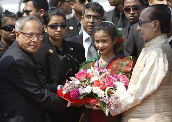 Visiting Indian President Pranab Mukherjee, left, is presented with flowers as he is received by his Bangladeshi counterpart, Zillur Rahman, right, upon his arrival at the airport in Dhaka.