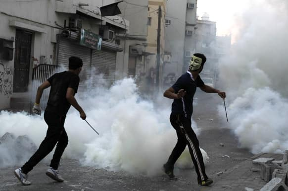 Bahraini anti-government protesters carry steel rods into clashes with riot police firing tear gas and birdshot in Manama, Bahrain.
