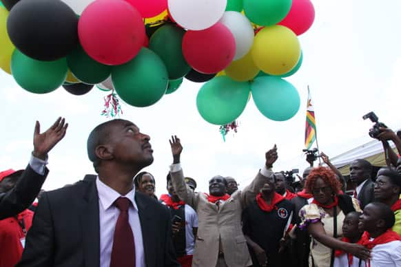 Zimbabwean President Robert Mugabe, centre, releases balloons into the air during celebrations to mark his 89th birthday in Bindura about 100 kilometres north of Harare.