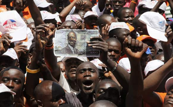 Kenyan Prime Minister and Presidential candidate, Raila Odinga`s supporters show a 1,000 Kenya shillings note featuring the picture of Raila Odinga as they gather at Nyayo National Stadium, Nairobi for the final day of the campaign for the election.
