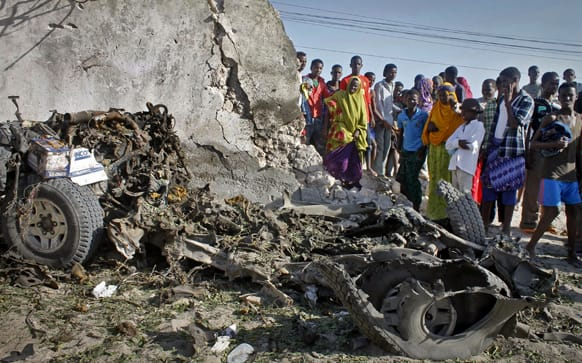 Somalis stand over the wreckage of a car following a blast at a restaurant near the beach in Mogadishu, Somalia.
