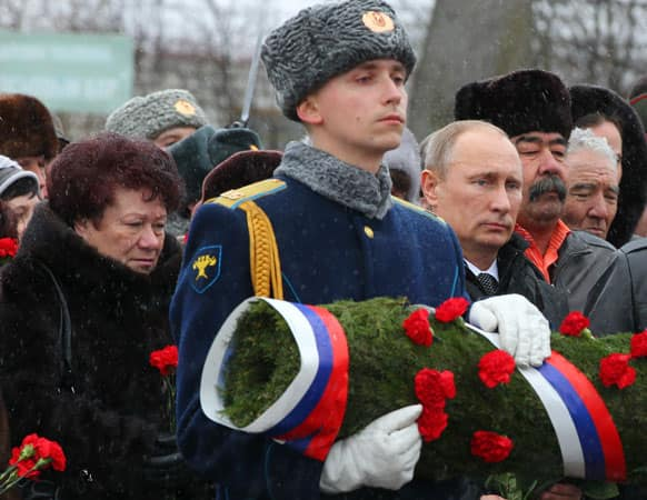 Russian President Vladimir Putin, third right, with relatives of Russian paratroopers who were killed in 2000 during the war in Chechnya, lays flowers at the monument to soldiers of the Pskov Airborne Division in Pskov, about 600 kms (375 miles) northwest of Moscow.