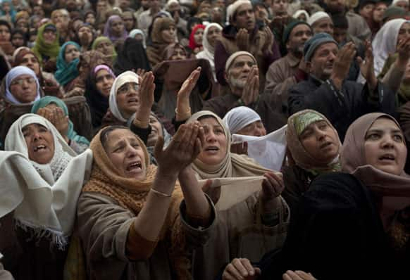 Kashmiri Muslim devotees pray as the head priest, unseen, displays a relic of Sufi saint Syed Abdul Qadir Jilani at his shrine in Srinagar.