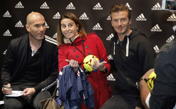 Soccer legend Zinedine Zidane, left, and Paris Saint Germain`s David Beckham pose for a photograph with unidentified fan as they sign autographs, during a media event, in a sports store, on the Champs Elysees Avenue, in Paris.