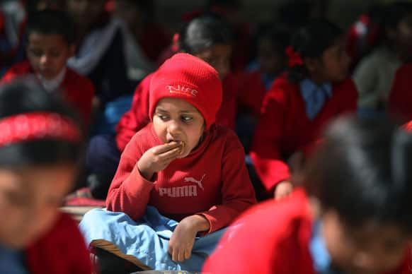Children eat a free mid-day meal at a government school on the outskirts of Jammu.