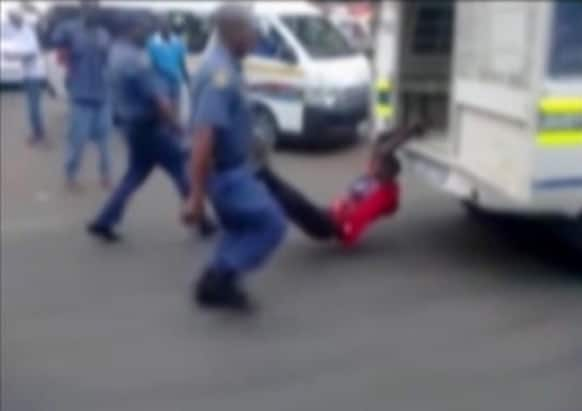 In this still frame from TV and courtesy of South African Daily Sun newspaper, showing a South African man with his hands tethered to the back of a police vehicle being dragged behind as police hold his legs up and the vehicle apparently drives off, east of Johannesburg.