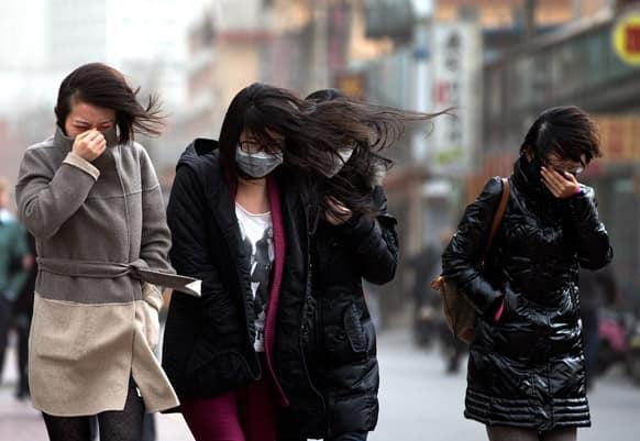 Chinese women, some wearing face masks, brace through strong wind after the capital city is hit by sandstorm in Beijing.
