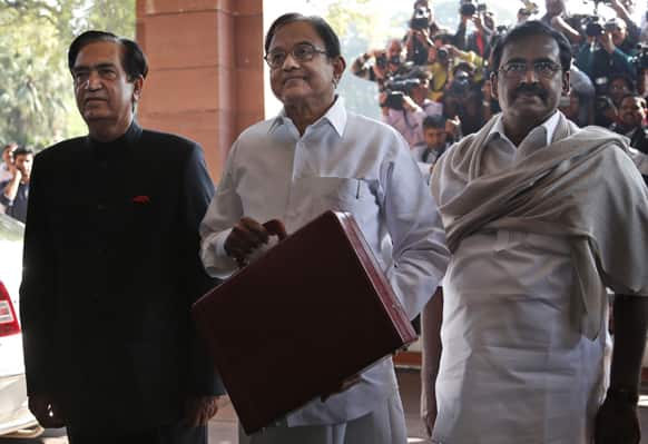 Finance Minister Palaniappan Chidambaram, center, arrives with his aides at the Indian Parliament to present the annual budget in New Delhi.