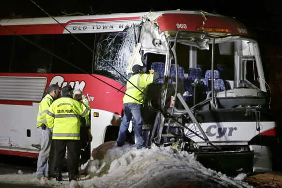 Massachusetts State Police examine the front of a crashed bus in Georgetown, Mass. The bus was carrying University of Maine basketball players and crashed into trees on the side of Interstate 95, north of Boston, injuring the driver and several students.