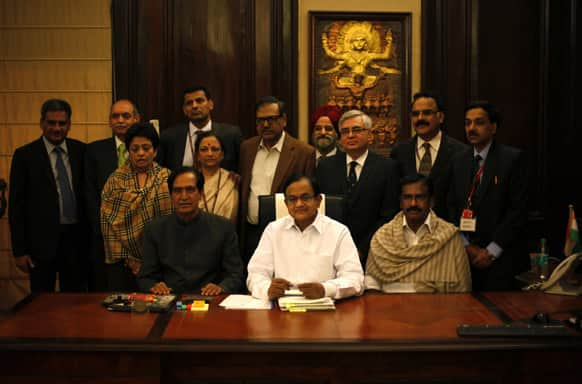 Finance Minister Palaniappan Chidambaram along with other finance ministry officials pose for photographs at his office in New Delhi.