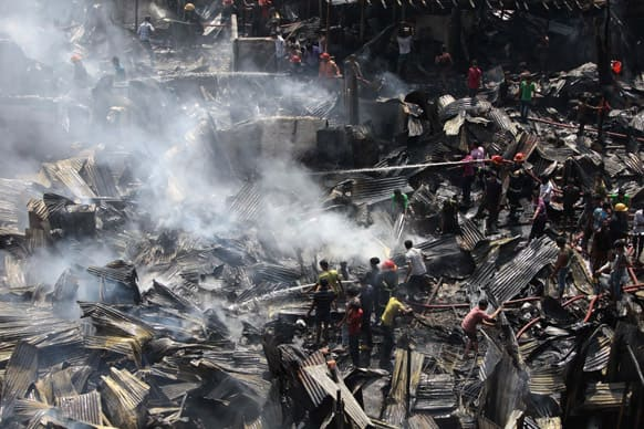 Bangladeshi firefighters and volunteers work to douse a fire at the Kallyanpur Natun Bazar slum in Dhaka. According to police, at least 300 shanties were gutted but there were no casualties.