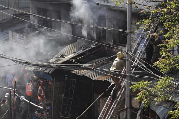 Firemen try to douse a fire that broke out early in the morning at an illegal six-story plastics market in Kolkata.