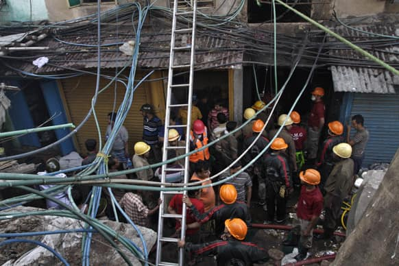 Firemen and rescuers wait outside an illegal six-story plastics market where a fire broke out early in the morning in Kolkata.