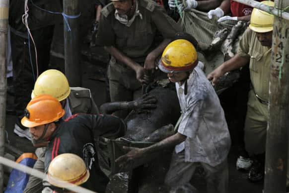 Rescuers carry a victim`s charred body after a fire broke out early in the morning at an illegal six-story plastics market in Kolkata.
