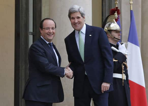 US Secretary of State John Kerry, right, is welcomed by France`s President Francois Hollande upon his arrival at the Elysee Palace, in Paris.