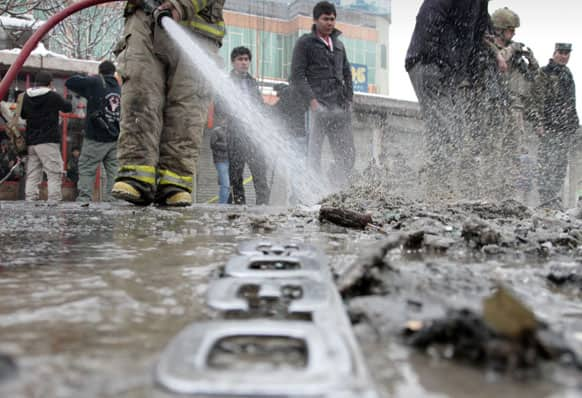 An Afghan firefighter hoses down the scene of a suicide bombing in Kabul, Afghanistan.