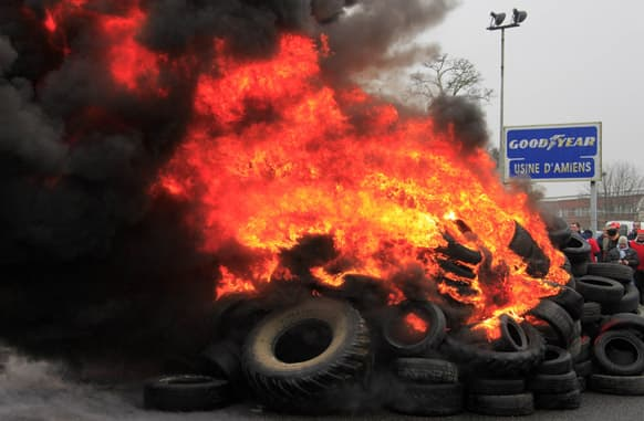 Goodyear employees gather around burning tires, outside the Goodyear tire company, in Amiens, northern France.