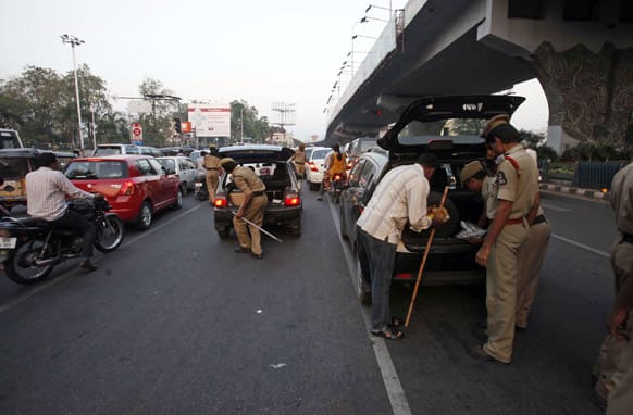 Policemen check belongings of motorists at a traffic signal after security was enhanced following Thursday's dual bomb attacks in Hyderabad.