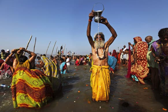 A devotee prays to the Sun God as others take holy dips at Sangam, the confluence of the Rivers Ganges, Yamuna and mythical Saraswati on Maghi Purnima, or the full-moon day, considered an auspicious bathing day, during the Maha Kumbh festival in Allahabad.