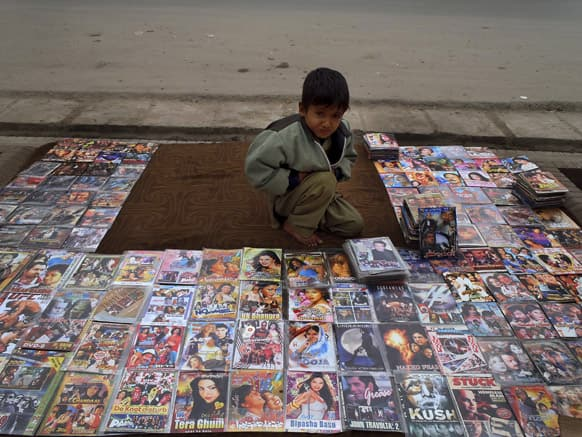 An Afghani boy, Ahmad Shah, 7, displays bootleg movies for sale along a road side in Jalalabad, Afghanistan.
