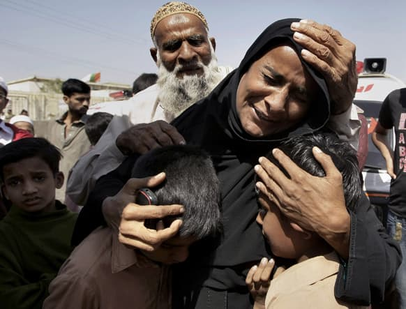 A Pakistani woman, Shahida Parveen, seen comforting her sons, mourns for her husband, Mohammad Akmal, a victim of a Sept. 11, 2012 factory fire incident, during a funeral in Karachi, Pakistan.