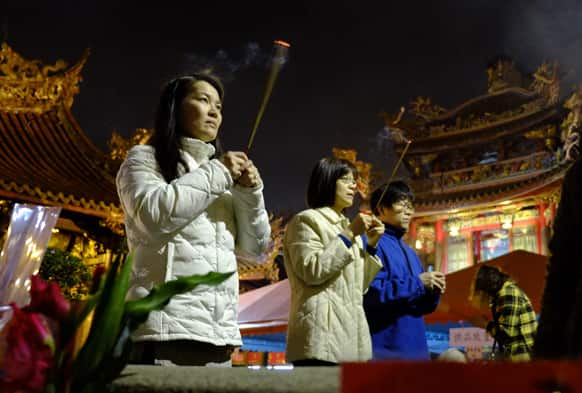 Devotees pray at the Lungshan Temple on the eve of the Chinese lunar new year in Taipei, Taiwan.