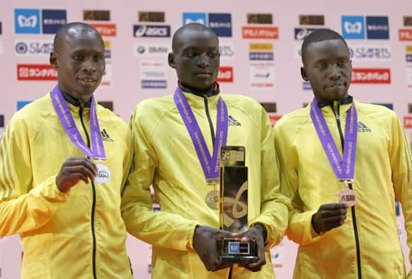Winner Dennis Kimetto of Kenya, poses with compatriots Michael Kipyego, who placed second and Bernard Kipyego who placed third, after the awards ceremony of the men`s Tokyo Marathon in Tokyo.