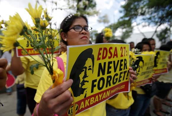 A Filipino activist displays flowers and slogans bearing an image of late Philippine strongman Ferdinand Marcos on the eve of the 27th anniversary of