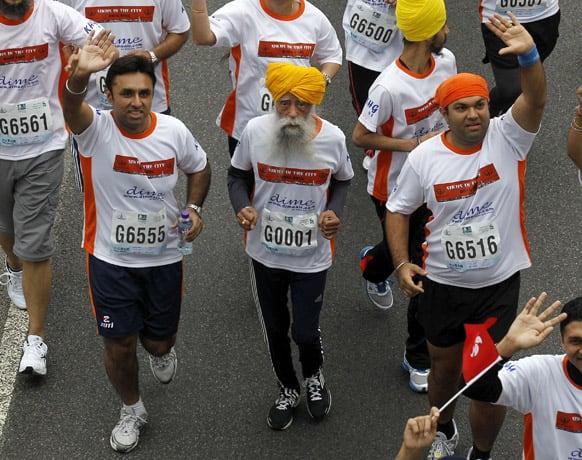 Centenarian marathon runner Fauja Singh, 101, center, originally from Beas Pind, in Jalandhar, India but who now lives in London, runs in a 10-kilometer race, part of the annual Hong Kong Marathon.