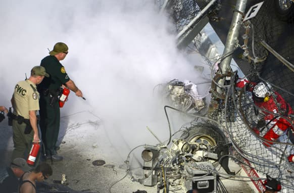 Emergency officials put out a fire from driver Kyle Larson`s engine after his car hit the wall and safety fence along the front grandstands on the final lap of a NASCAR Nationwide Series auto race at Daytona International Speedway in Daytona Beach, Fla.