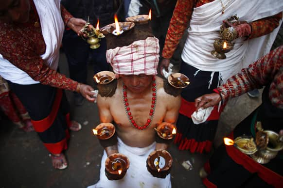 A Nepalese Hindu devotee balances lit lamps along his arms during the Madhav Narayan Festival in Lalitpur, on the outskirts of Katmandu, Nepal.