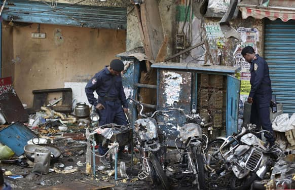 Officials of India`s National Investigation Agency look for evidence in the debris at one of the two bomb blast sites, in Hyderabad.