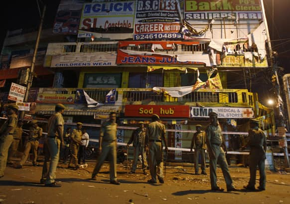 Policemen guard a shopping arcade, damaged in one of the two bomb blasts, in Hyderabad.