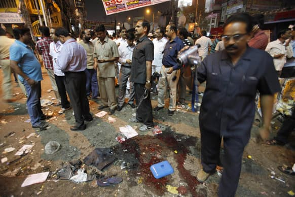 A police employee records the scene after a bomb blast in Hyderabad.